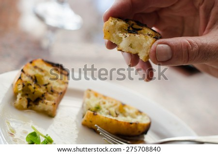 Hand is holding a piece of toasted garlic bread with garlic bread on a plate in the background - stock photo
