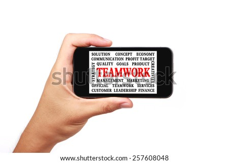 Hand is holding a smart phone with the teamwork word cloud isolated on white. - stock photo