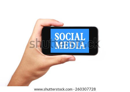 Hand is holding a smart phone with the text Social media isolated on white. - stock photo