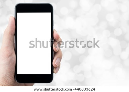 Hand is holding a smartphone with white blank screen over the bright grey bokeh. Copy space on a right hand side. - stock photo