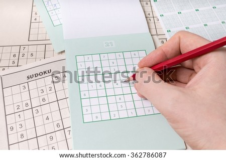 Hand is holding pencil and is solving sudoku crossword with numbers.