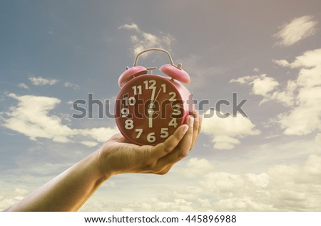 Hand is holding retro alarm clock on sky background.