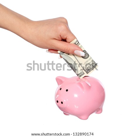 hand is putting money into piggy bank isolated on white, saving money