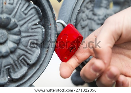 hand is showing a red padlock with heart - stock photo