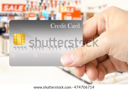 hand is showing the gray credit card on sale  period of department store background.