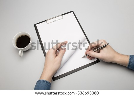 Hand is signing on a blank clipboard