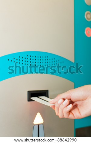 Hand is slipping parking ticket into pay machine - close-up - stock photo