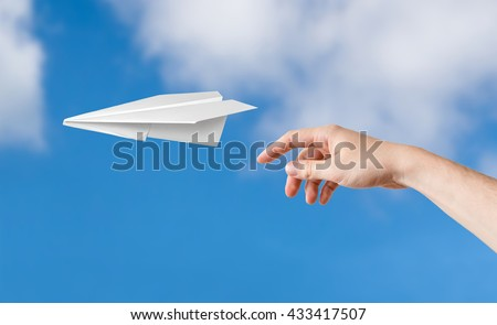 Hand is throwing origami paper airplane. Blue sky on background.
