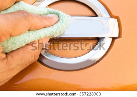 Hand is using a polishing cloth clean the car, Car cleaning background.