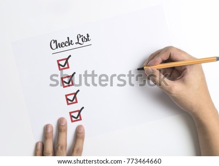 Hand is writing and checking the Checklist on paper