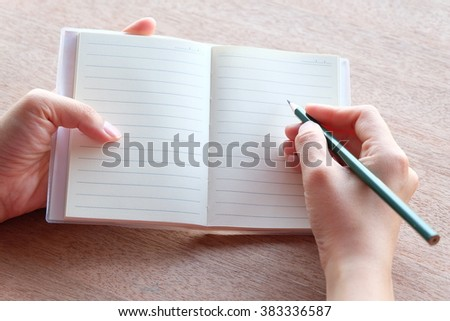 hand is writing on blank notebook on wood textures