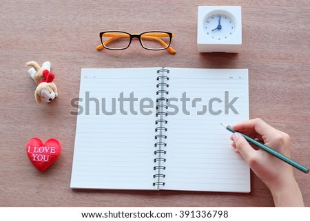 hand is writing on blank notebook with red heart, glasses and alarm clock, on wood textures