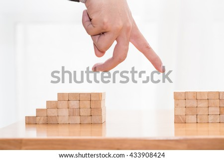 Hand jump through the gap between wood block, Jump over obstacles concept - stock photo