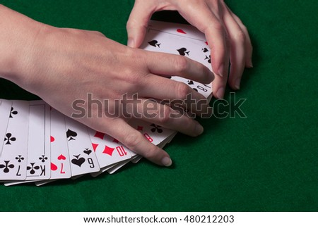 hand lays out a deck of playing cards on a table