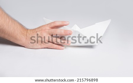 Hand leaves paper ship on the ground