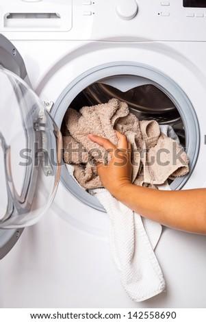 Hand loading laundry to the washing machine - stock photo