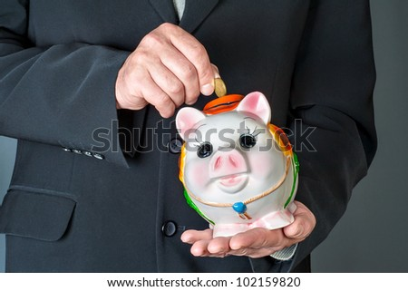 hand lowering a coin in a moneybox - stock photo