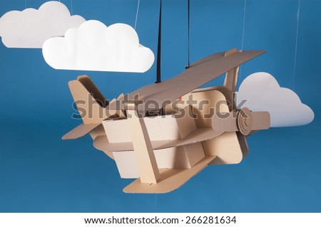 Hand made airplane made of cardboard on blue sky with paper clouds. - stock photo