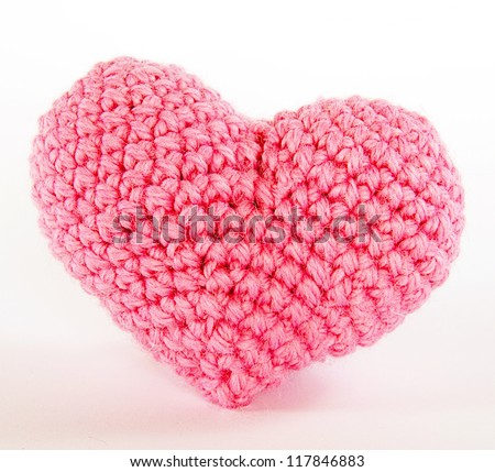 Hand made amigurumi crochet knit pink heart. Isolated on white background