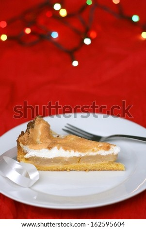 Hand made christmas apple pie with whipped egg white, christmas lights in the background, shallow DOF - stock photo