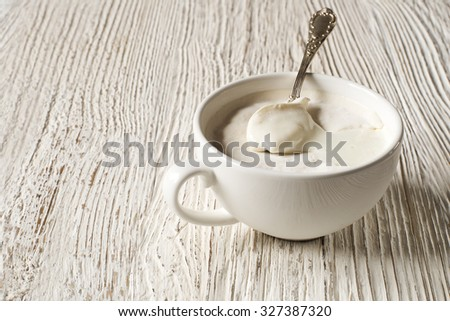 Hand-made cream yogurt in a bowl with spoon. - stock photo