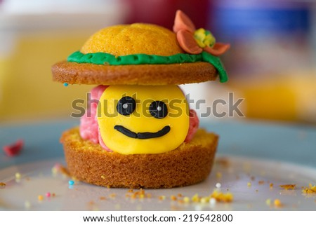 Hand made cup cake with a smiley face and crumbs - stock photo