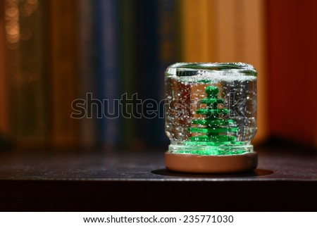 hand made snow globe with little green pine tree and glitter - stock photo