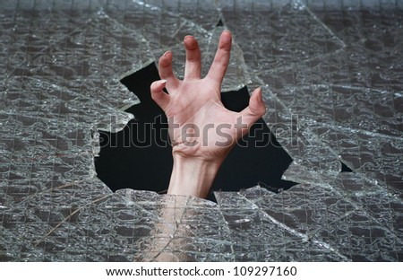 hand make their way through the broken glass - stock photo