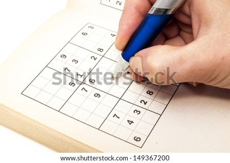 hand making a sudoku on a white background - stock photo