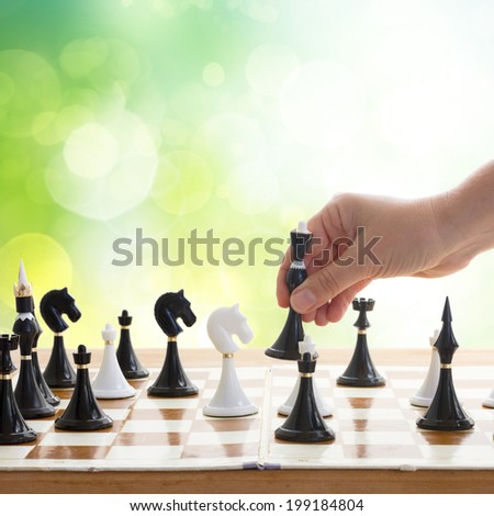 hand making move in chess game with black queen in green garden