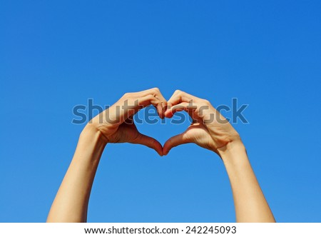 Hand making the sign of Love with the blue sky background.