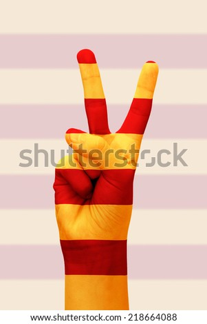 Hand making the V sign with the Catalan flag painted as symbol of victory - stock photo