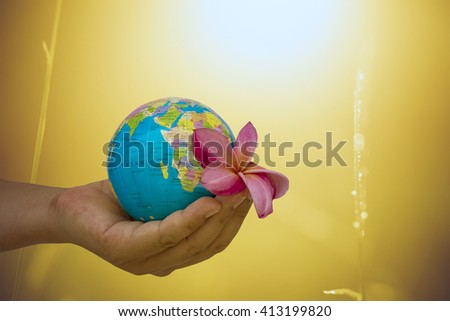 hand male gesture holding the world against blur of green background, human hands with healthy world concept, love and safe conception. - stock photo