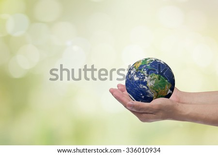 hand male gesture holding the world against blur of green foliage with bulbs light background:human hands with healthy world concept:love and safe conception.Elements of this image furnished by NASA - stock photo