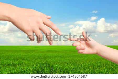 hand man and a child hand drawn to each other on the background of green field and blue sky