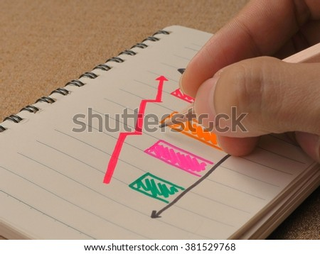 Hand man drawing a growing graph on notebook - stock photo