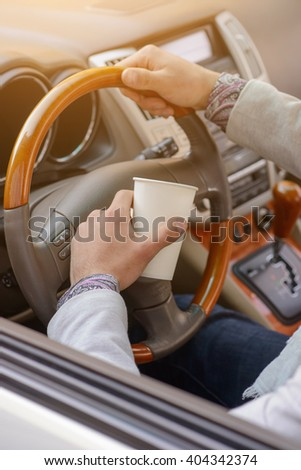 hand man driving an expensive car with a cup of coffee - stock photo