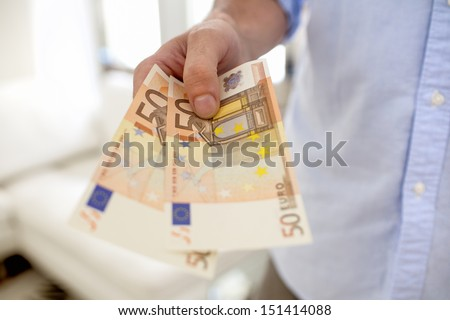 Hand man holding fifty banknotes euro indoor - stock photo