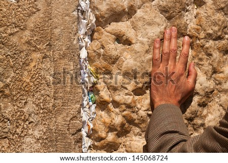 Hand man praying at the Wailing Wall with notes in the wall with requests - stock photo