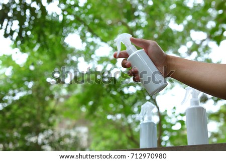 hand man using foggy spray water bottle showing product with abstract blur green bokeh nature background
