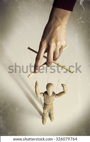 Hand manipulating a puppet on a dark background scratched - stock photo