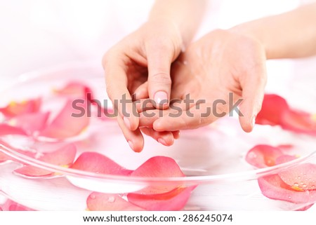 Hand massage, acupressure.  Beauty ritual for hands. Care treatment of hands and nails woman hands over the bowl with rose petals  - stock photo
