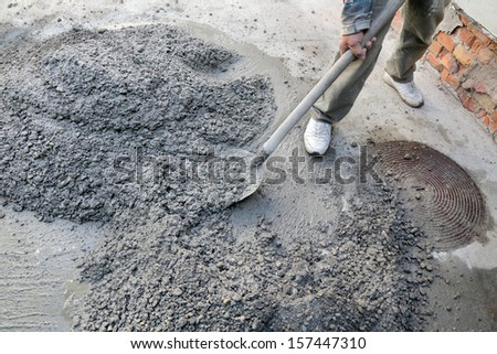 Hand mixing concrete with worker and shovel - stock photo