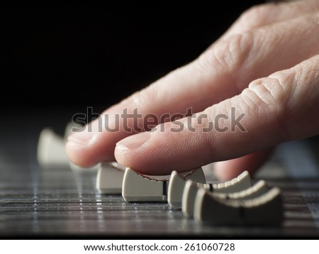 Hand moving  faders of the mixing desk, for music,sound,entertainment themes - stock photo