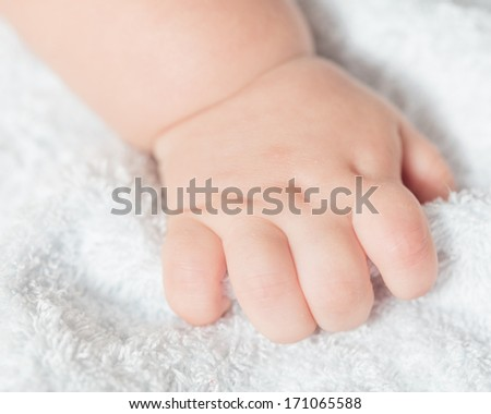 Hand of a baby on terry background