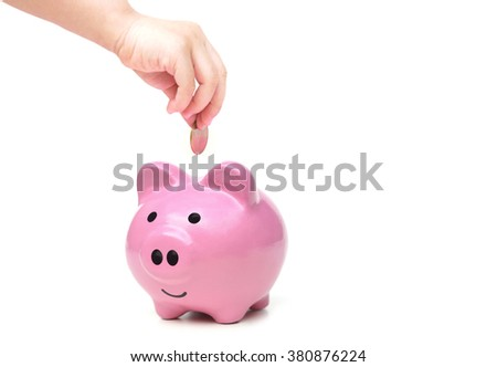 hand of a baby putting a coin into a pink piggy bank