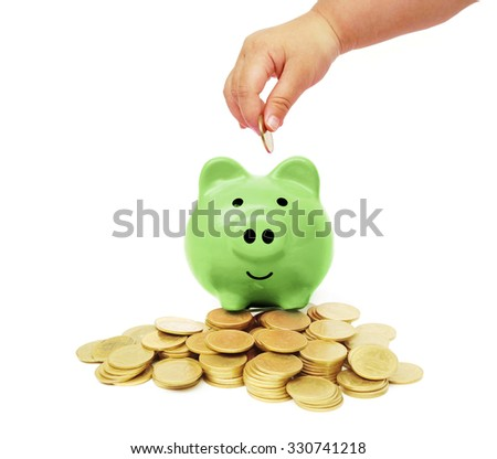hand of a baby putting a golden coin into a green piggy bank with piles of golden coins arranged as a graph