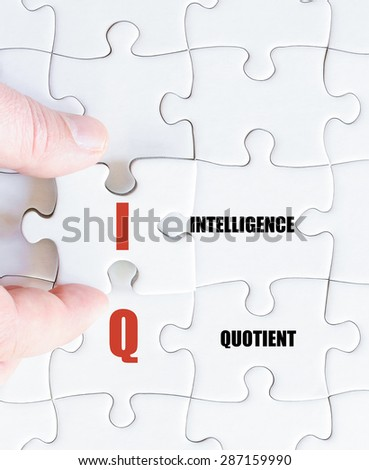 Hand of a business man completing the puzzle with the last missing piece.Concept image of Business Acronym IQ as Intelligence Quotient - stock photo