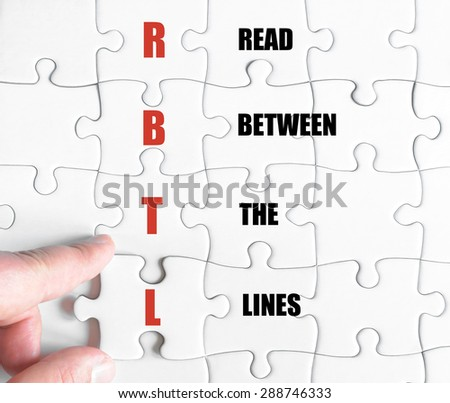 Hand of a business man completing the puzzle with the last missing piece.Concept image of Business Acronym RBTL as Read Between The Lines
