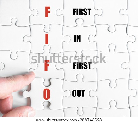 Hand of a business man completing the puzzle with the last missing piece.Concept image of Business Acronym FIFO as First In First Out